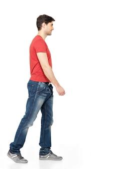흰 벽에 고립 된 빨간 티셔츠 캐주얼에 웃는 걷는 남자의 전체 초상화.