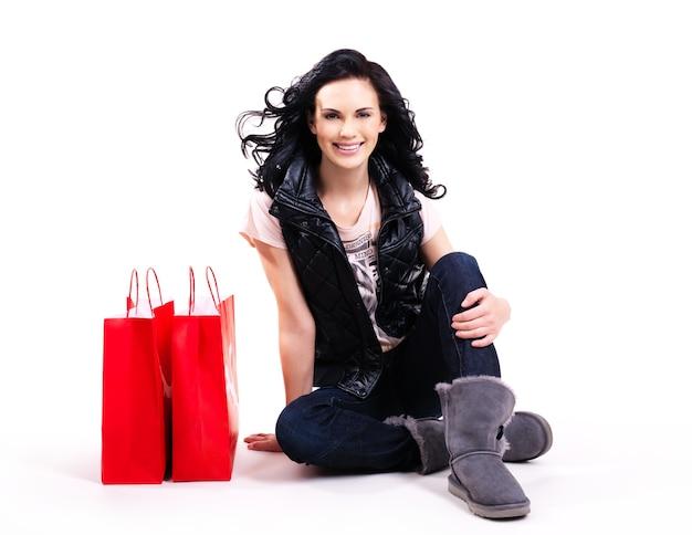 흰색 절연 바닥에 앉아 빨간 쇼핑백과 웃는 여자의 전체 초상화.