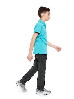 白で隔離の青いtシャツカジュアルで歩く十代の少年の完全な肖像画。