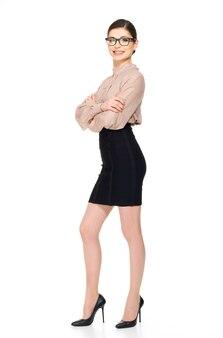 白いシャツと白い背景で隔離の黒いscirt立っている若い美しい女性の完全な肖像画。