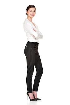 Полный портрет молодой красивой женщины в белой рубашке и стоя черных брюках.