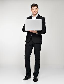 Ritratto completo dell'uomo d'affari felice sorridente con il computer portatile in vestito nero