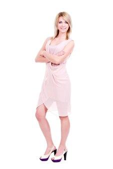 Ritratto completo di giovane donna sorridente in abito rosa in piedi - isolato