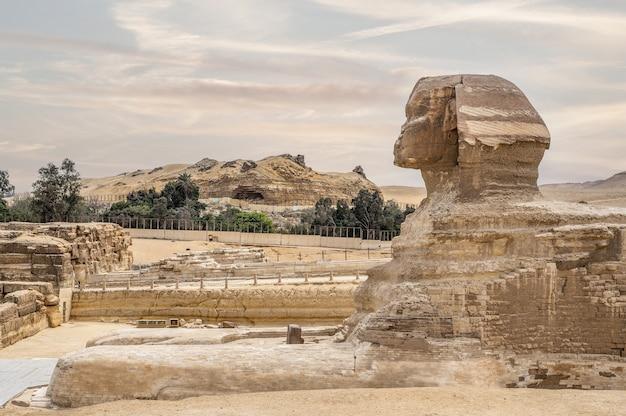 エジプト、カイロ、ギザの曇り空の日の背景にあるカフラー王のピラミッドを含むグレートスフィンクスの全プロフィール。無人。夕焼けの空を背景にスフィンクスの頭、あなたのテキストのためのスペース