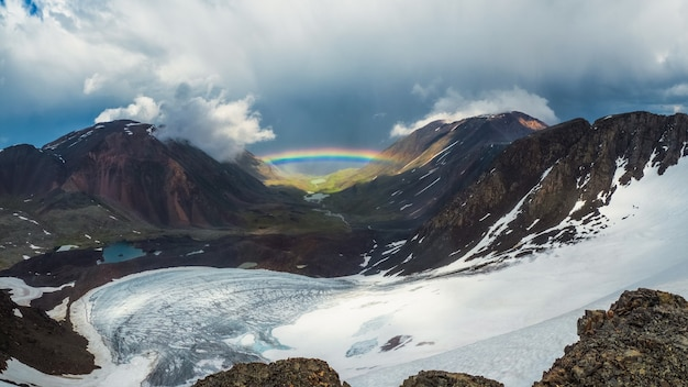 氷河の山の谷の上の完全な虹。雨と晴れの天気で虹と雪に覆われた山々と大気の高山の風景。