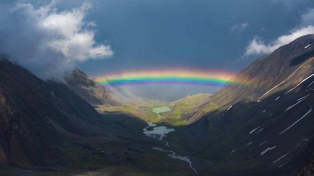 山の谷の上の完全な虹。雨と晴れの天気で虹と雪山と大気高山の風景。