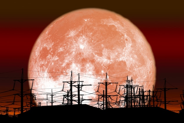 Full red milk moon back on silhouette electric pole on night sky
