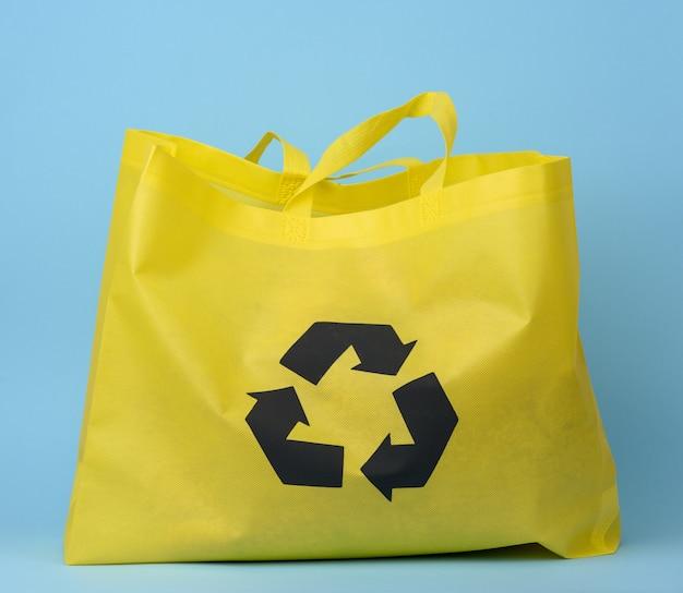 Полный многоразовый желтый мешок из вискозы на синем фоне, концепция сокращения пластиковых отходов