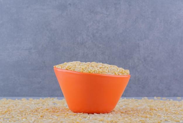 Ciotola di riso piena seduta su una massa sparsa di riso integrale su una superficie di marmo