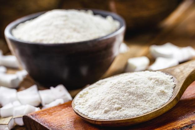 Полная деревенская деревянная ложка и кокосовая мука, кулинарный ингредиент.