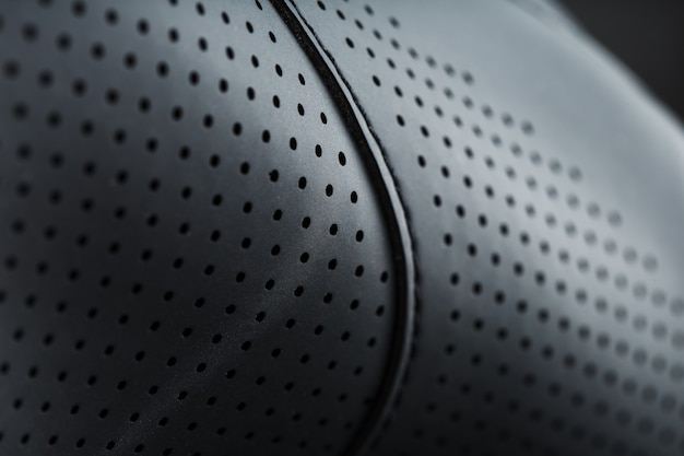 Full-screen close-up of black perforated leather. texture material in macro