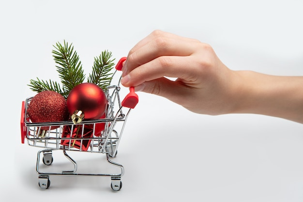 Full shopping cart. christmas toys, gifts and spruce branch in the buyer's basket.