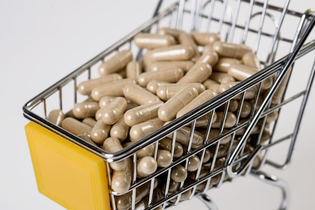 Full shopping cart of medicine, pharmaceutical capsules on white surfa