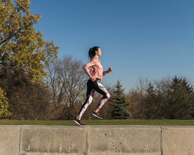 Full shot active woman running outdoor