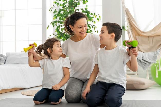 Full shot adulto e bambini con manubri
