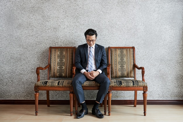 Full shot of adult pensive businessman sitting on couch and looking down