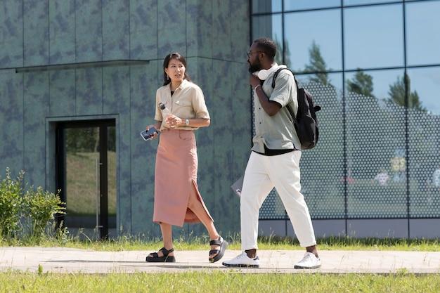 屋外で一緒に歩くフルショットの大人