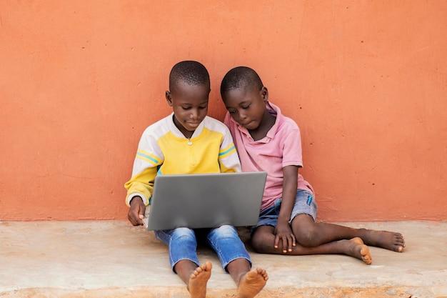 Bambini africani del colpo pieno con il computer portatile