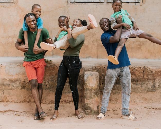 一緒にポーズをとるフルショットのアフリカの人々