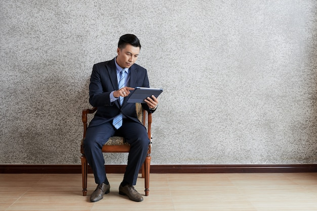 Full shot of asian businessman using tablet pc seated in armchair in an empty room