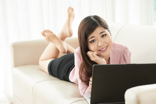 Full shot of an asian freelance worker lying on couch at the laptop looking at camera
