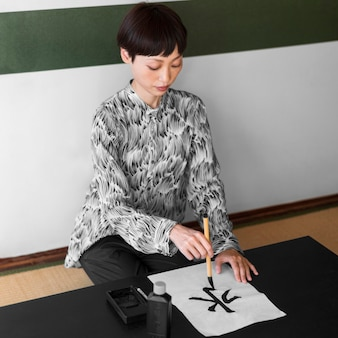 Full shot asian woman painting letter