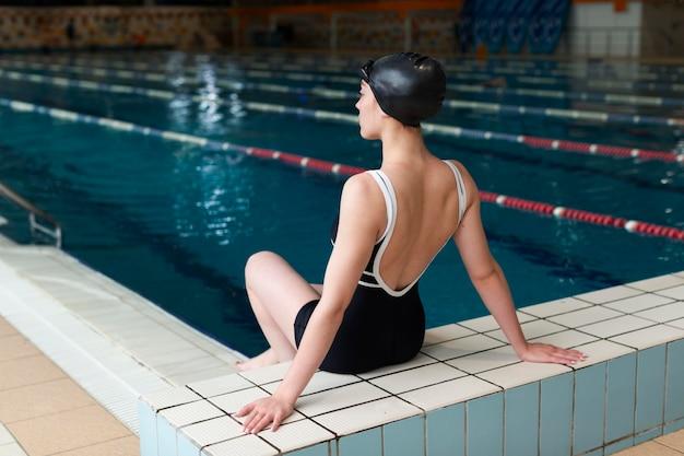 Full shot athlete on the edge of pool