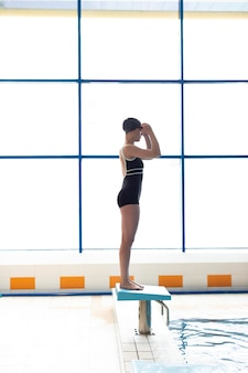 Full shot athlete ready to jump in pool