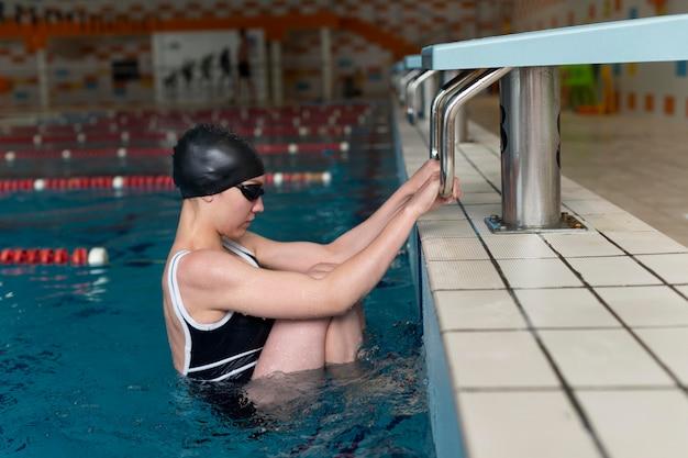 Full shot athlete wearing swim cap and goggles