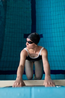 Full shot athlete with goggles in pool