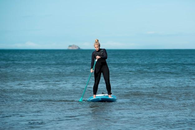 Full shot athletic woman paddleboarding
