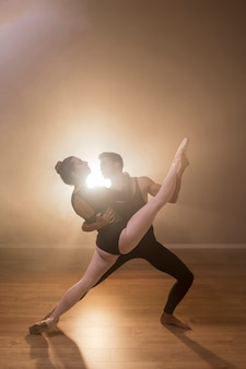 Full shot ballerina being held by male dancer