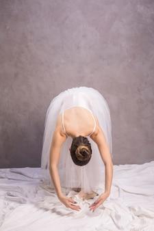 Full shot ballerina bending over