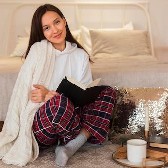 Полный снимок красивой женщины, сидящей на ковре с книгой