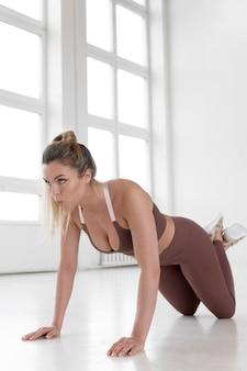 Full shot of blonde woman doing calisthenics