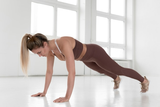 Full shot of blonde woman doing  plank