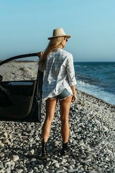 Donna bionda del colpo pieno che esamina il mare in macchina
