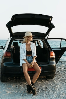 Full shot blonde woman standing in car trunk with juice bottle