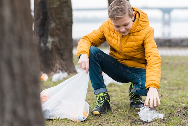 Full shot of boy cleaning the ground