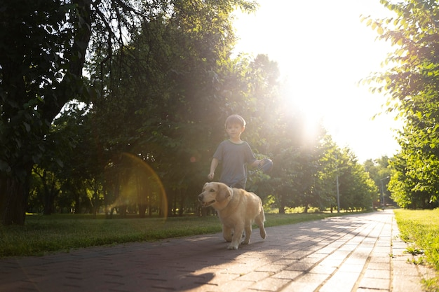 Full shot boy and dog in park