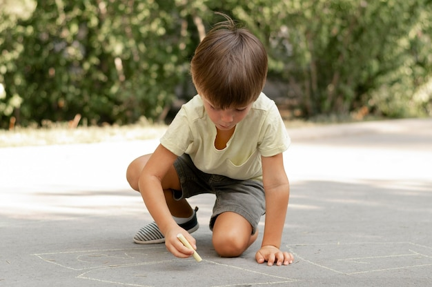 Full shot boy drawing on ground