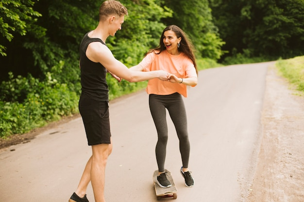 Full shot boy helping girl skateboarding