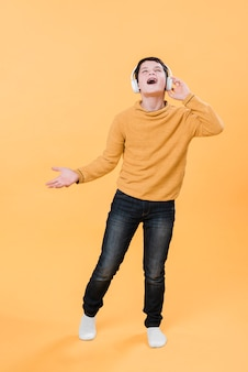 Full shot of boy listening to music with headphones