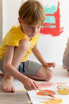 Мальчик в полный рост, рисующий на бумаге