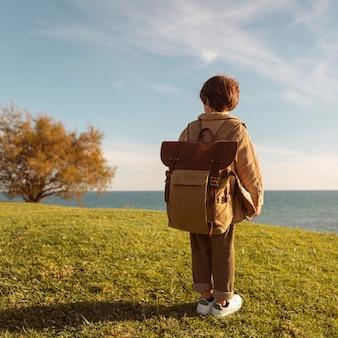 バックパックを身に着けているフルショットの少年