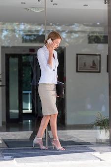 Donna piena di affari del colpo che parla sul telefono