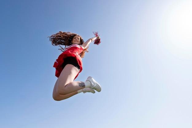屋外でジャンプするフルショットチアリーダー