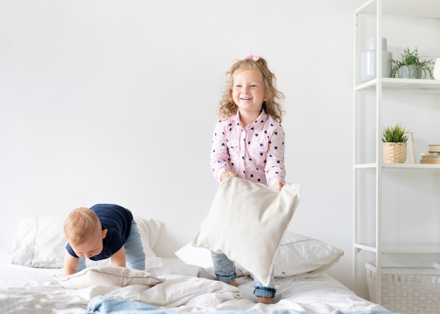 Full shot children playing with pillows
