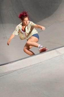 Bella donna a tutto campo sullo skateboard