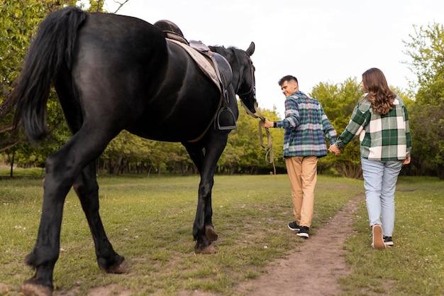 フルショットのカップルと屋外の馬